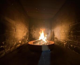 Bildet viser brannrommet med bål av påtente trepaller.
